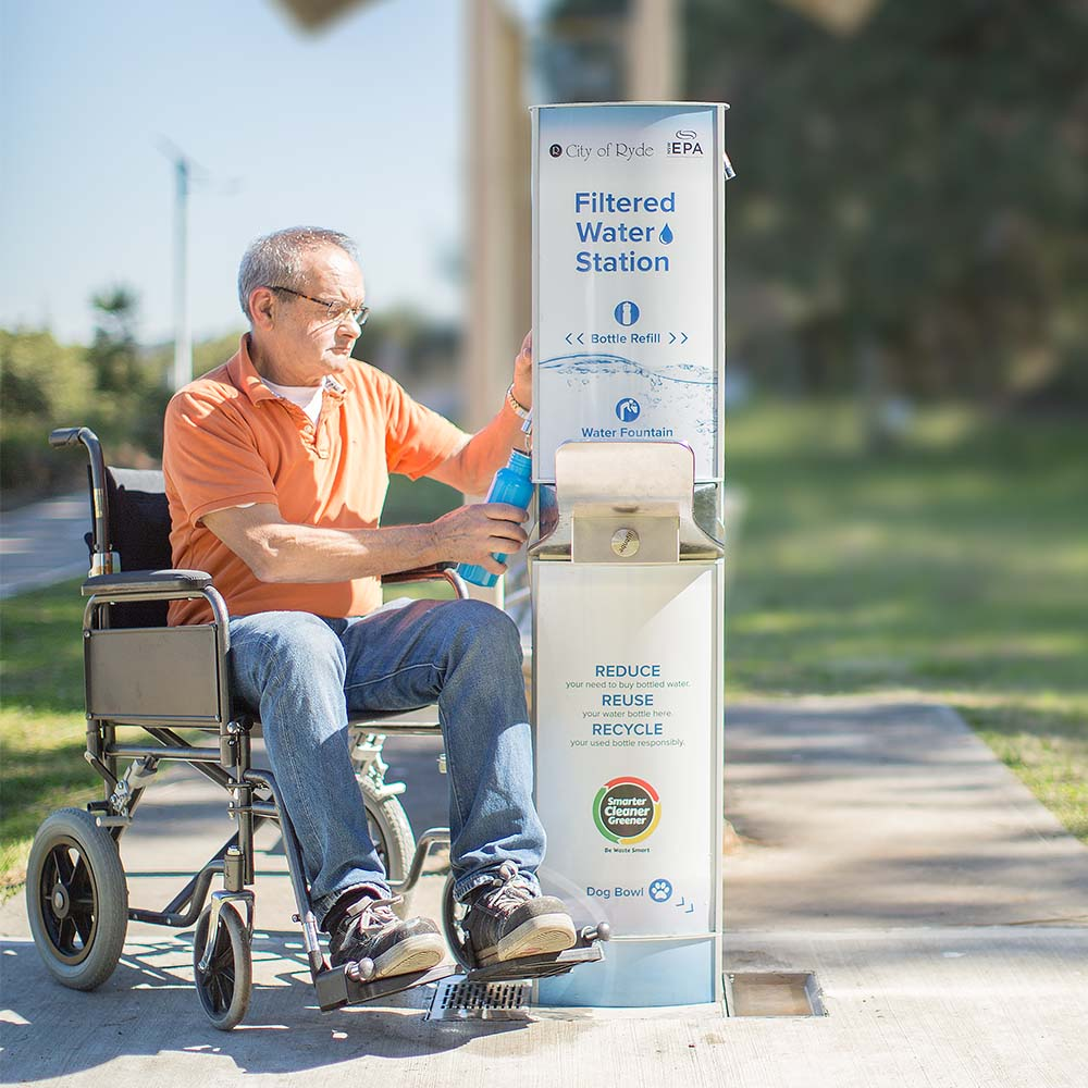 An old man on a wheelchair refilling his water bottle on a Drinking fountain installed at City of Ryde