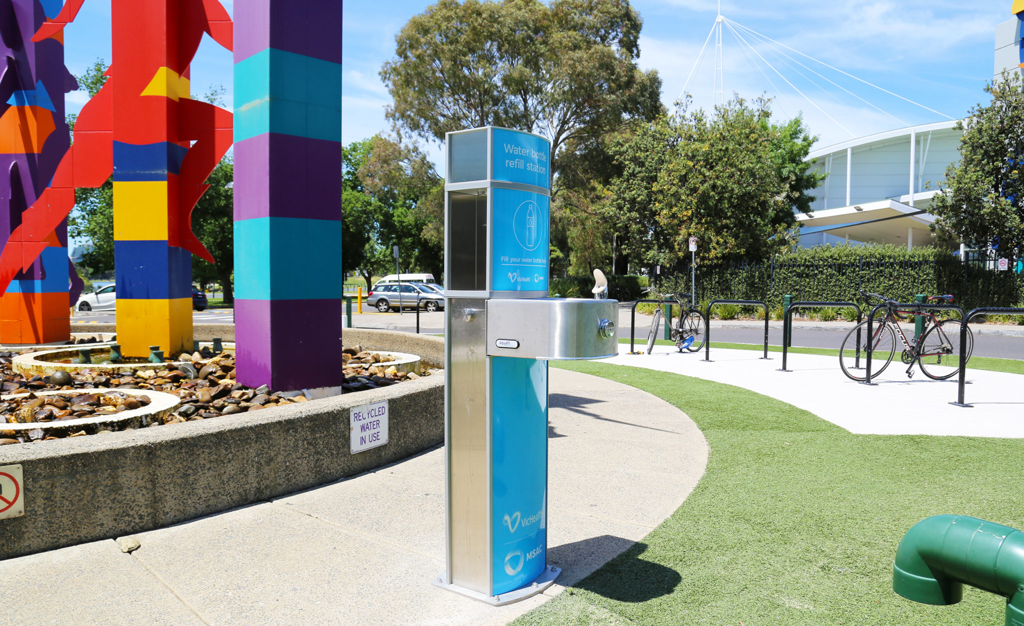A side view of the Outdoor  drinking water stations with blue artwork installed near a fountain out the front of Melbourne Sports and Aquatic Centre
