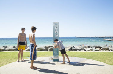 An Outdoor Shower with Drinking Fountain installed at the Busselton Foreshore and in use by three kids