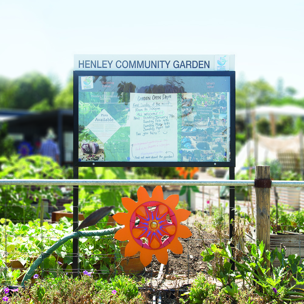 Henley Community Garden displaying a free standing community notice board with a public announcement for the Garden Opening hours