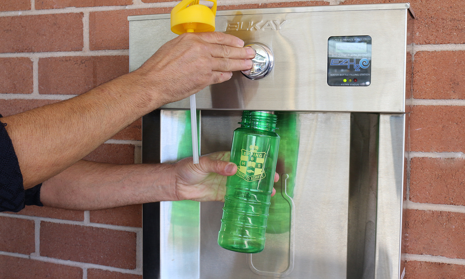A man refilling his bottle on an elkay EZH20 water bottle filling station