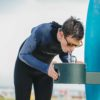 A teenager surfer boy drinking from Elkay Outdoor Water Bottle Filling Station and Drinking Fountain Bi-Level