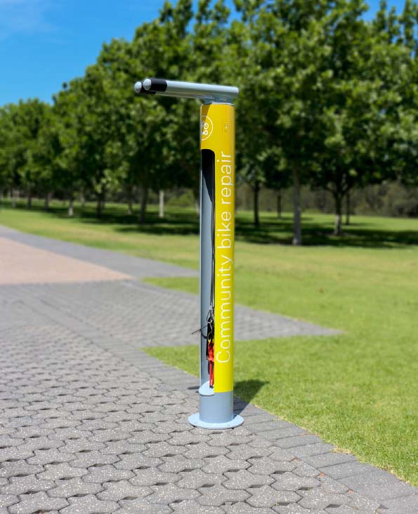 Cycla Fixit Bike Repair Station bolted into the pavement in Yellow Color with a caption community bike repair