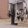 a family walking their dog on a black Elkay EZH2O Outdoor Water Bottle Filling Station and Drinking Fountain Bi-Level, Pedestal with Pet Station