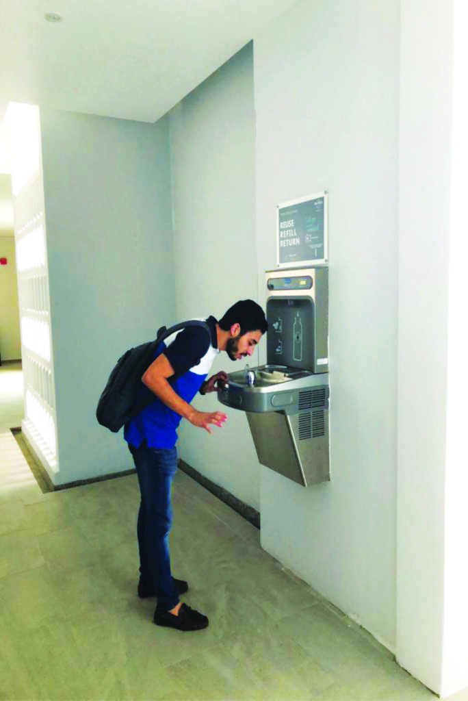 a man drinking and utilising Elkay wall mounted Drinking Fountain
