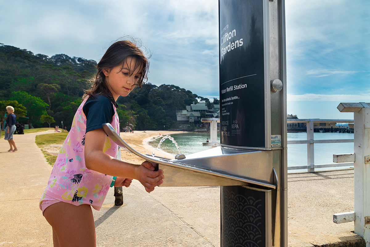 A girl using CIVIQ Drinking Water Stations installed at Clifton with Hygienic Features for Healthy Communities.