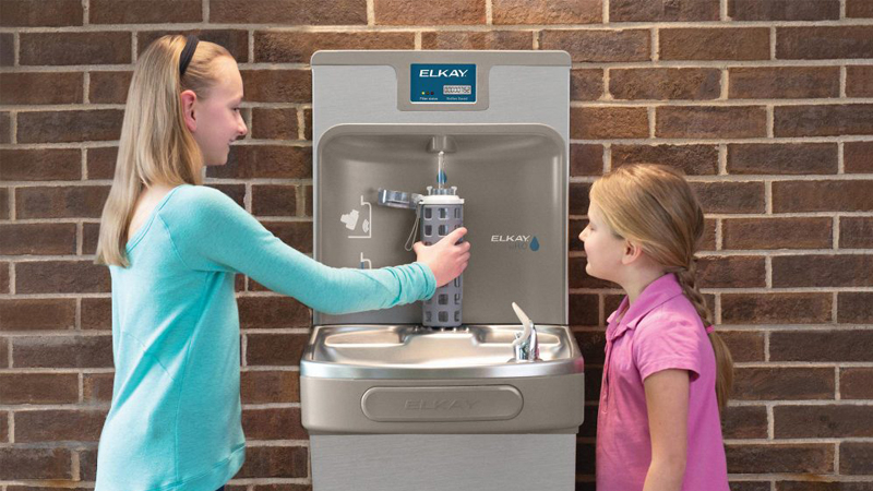 Two children refilling their bottled water from Elkay Drinking Fountain as part of plastic free July