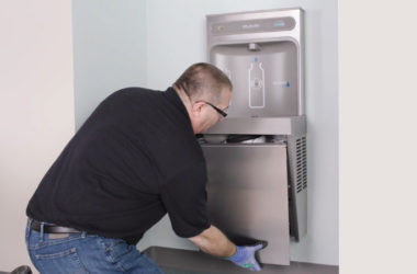 a man installing an elkay drinking water station for Extended Closure Reopening guide