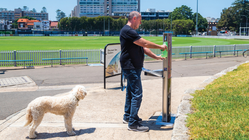 a man with his dog refilling his water bottle in a water dispensing product from CIVIQ